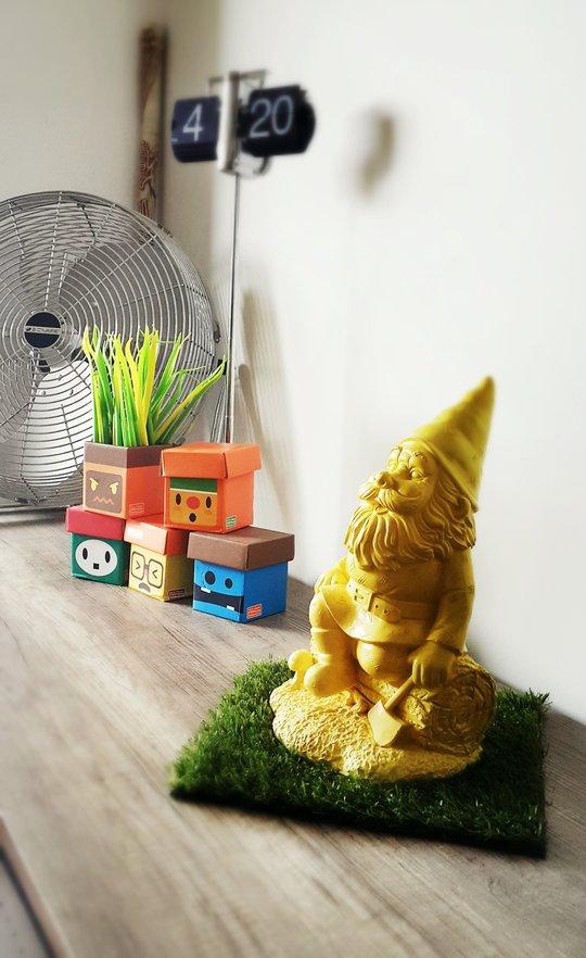 des stylos herbe dans une boite manemo et un nain de jardin
