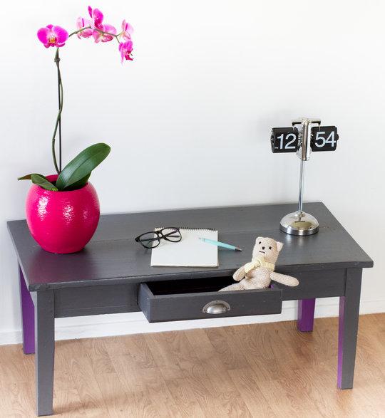 Une table basse grise avec les revers des pieds en violet
