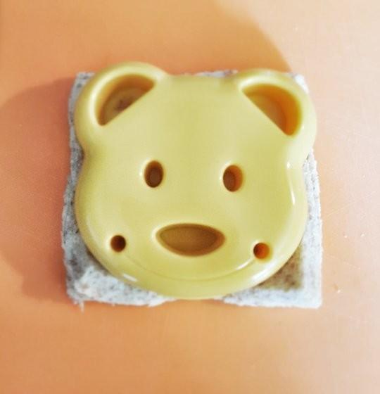Un decoupe sandwich en forme d'ourson depose sur un sandwich pour la decoupe.